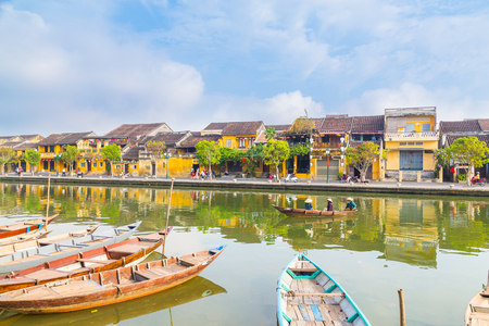 HOI AN, VIETNAM - 25TH MARCH 2017: A view of the Hoi An Ancient from across the Thu Bon River during the morning. Buildings, boats, reflections and locals can be seen.