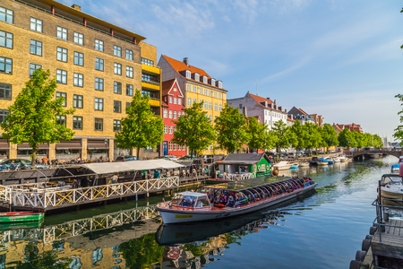 COPENHAGEN, DENMARK - 23RD MAY 2017: Buildings and boats along the Christianshavn Canal in Copenhagen. Lots of people can be seen on the boat. Editorial