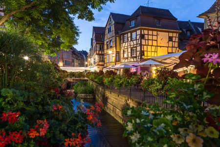 COLMAR, FRANCE - 31ST JULY 2016: Beautiful streets of Colmar at night. Old Colorful timber framed architecture and flowers can be seen.