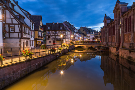 COLMAR, FRANCE - 31ST JULY 2016: A view of colourful timber framed buildings and part of Marché couvert de Colmar at night. Reflections can be seen. Editorial