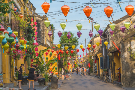 HOI AN, VIETNAM - 24TH MARCH 2017:  Colourful architecture and lanterns along streets of Hoi An Ancient Town during the day. People can be seen. Editorial