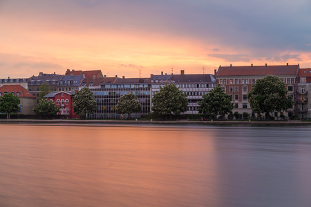 COPENHAGEN, DENMARK - 23RD MAY 2017:  A view along the Peblinge So lake in Copenhagen around sunset. Buildings and a colourful sky can be seen.