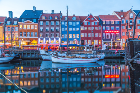 COPENHAGEN, DENMARK - 22ND MAY 2017: Architecture and boats along the Nyhavn in the early evening. Reflections and people can be seen.