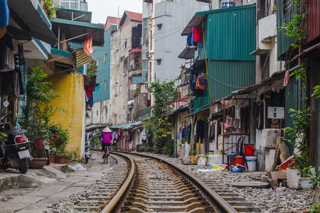 HANOI, VIETNAM - 19TH MARCH 2017: A view along train tracks running through the city of Hanoi. The outside of buildings and people can be seen along the side. Editorial