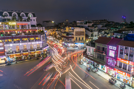 HANOI, VIETNAM - 20TH MARCH 2017: Trails of light from large amounts of traffic in central Hanoi at night. The outside of buildings and people can be seen.