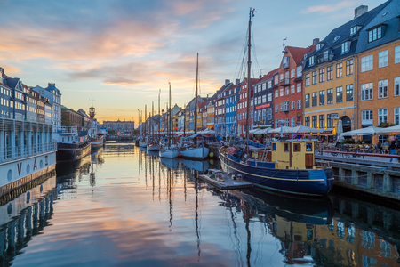 COPENHAGEN, DENMARK - 22ND MAY 2017: View of boats and buildings along the Nyhavn at sunset with colourful clouds and reflections. People can be seen. Editorial