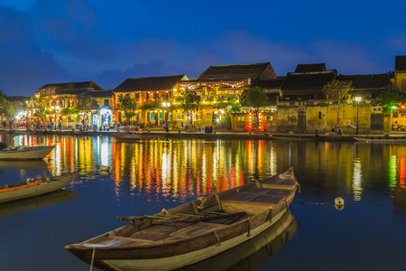 HOI AN, VIETNAM - 24TH MARCH 2017: A view over the  Thu Bon River towards Bach Dang street in Ancient Town. Colourful lights, buildings, reflections and people can be seen. Editorial