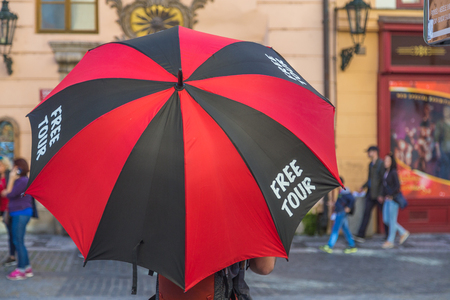 PRAGUE, CZECH REPUBLIC - 15TH OCTOBER 2017: A man holding an umbrella in Pragues Old Town that says