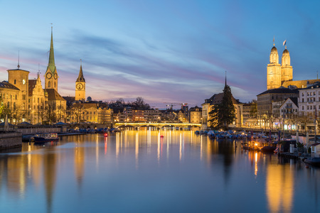 Classic views of the Zurich skyline at long the Limmat river at sunset and into the blue hour. The Grossmünster, Fraumünster and St. Peter Church can be seen.