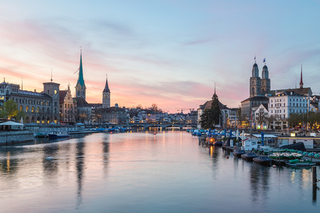 Classic views of the Zurich skyline at long the Limmat river at sunset. The Grossmünster, Fraumünster and St. Peter Church can be seen.