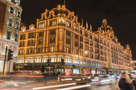 LONDON, UK - 25TH NOV 2018: The outside of Harrods department store in Knightsbridge London at Christmas. Showing large amounts of festive decorations on the building. People can be seen.