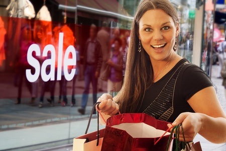 young and beautiful woman with shopping bags infront of shopping window photo