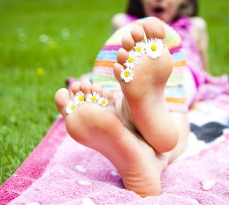 leaxing feets in meadow