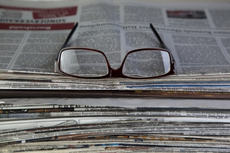 unsubscribe: newspaper with reading glasses Stock Photo