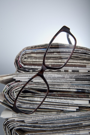 magazine stack: newspaper with reading glasses Stock Photo
