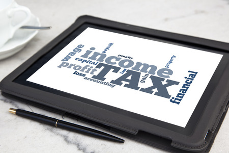 tablet with tax word cloud photo