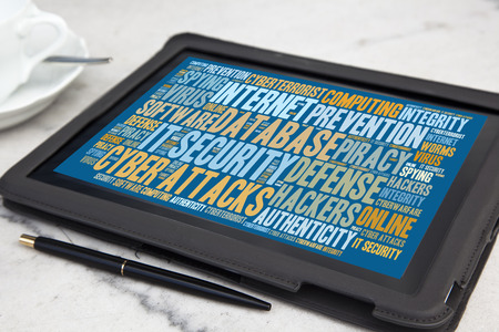 cyberwarfare: tablet with it security word cloud Stock Photo