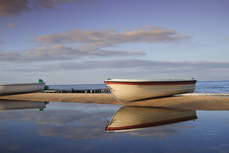 tourismus: White fisherboat on the sand