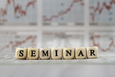 Seminar word built with letter cubes on newspaper background photo