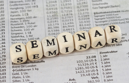 Seminar word built with letter cubes on newspaper background Stock Photo