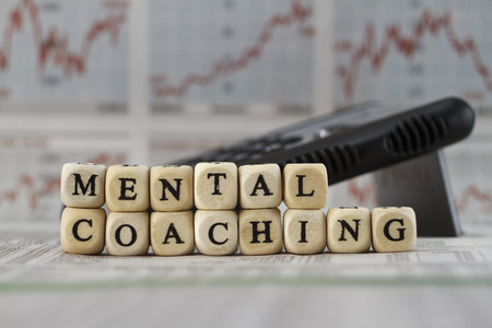 Mentalcoaching built with letter cube on newspaper background Stockfoto