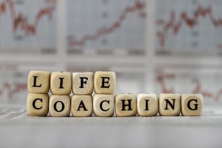 新聞の背景に文字キューブで建てられた単語のコーチング