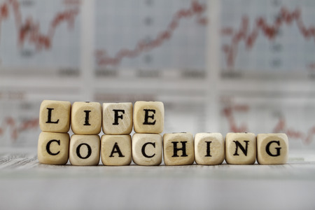 life coaching: Life Coaching word built with letter cubes on newspaper background