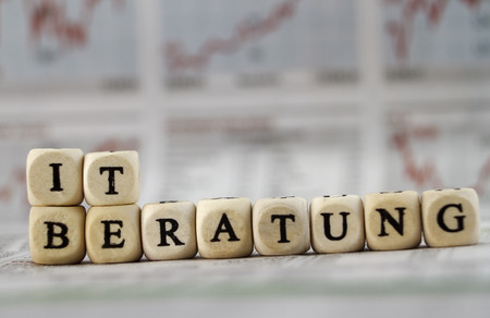 IT consultancy Built with letter cubes on newspaper background photo