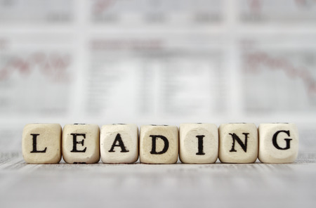 Leading word built with letter cubes on newspaper background