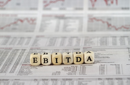 depreciation: EBITDA word built with letter cubes on newspaper background