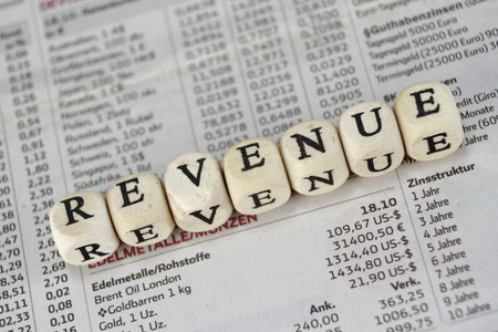 marginal: Revenue built with letter cubes on newspaper background
