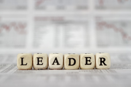 Leader Word Built with letter cubes on newspaper background