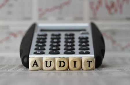tax consultants: Audit word built with letter cubes on newspaper background Stock Photo