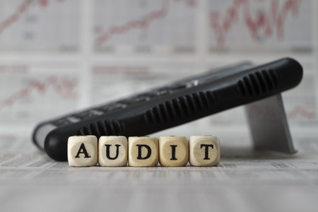 audit: Audit word built with letter cubes on newspaper background Stock Photo