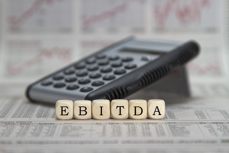 amortization: EBITDA word built with letter cubes on newspaper background