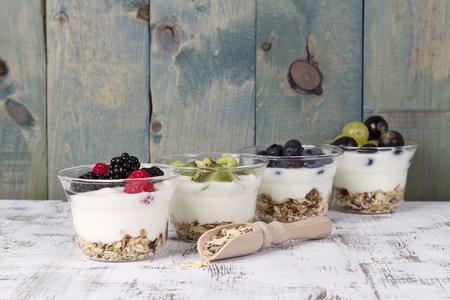 yogur: yogur de frutas con arándanos, frambuesas, arándanos, uva y muesli Foto de archivo