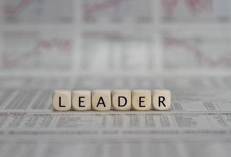loss leader: Leader word built with letter cubes on newspaper background Stock Photo