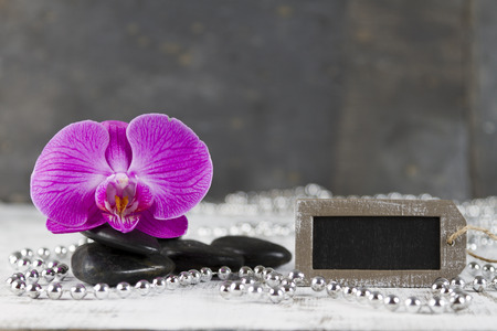 esotericism: wellbeing concept with hot stones and pink orchid Stock Photo