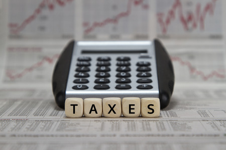 withholding: Taxes word with calculator on newspaper background