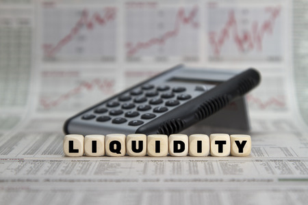 liquidity: Liquidity word with calculator on business newspaper Stock Photo