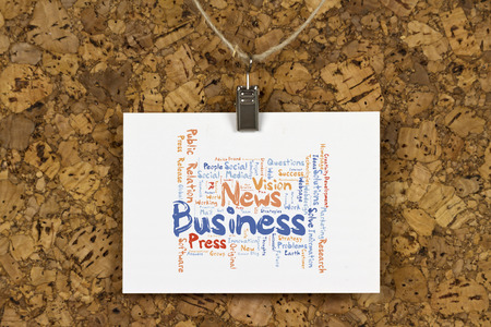 Business News word cloud on business card pinned up on cork board