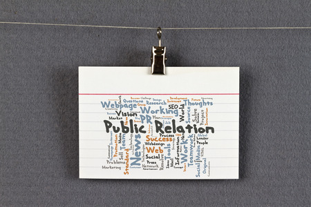 public relation: Public Relation word cloud on a business card pinned up on a board