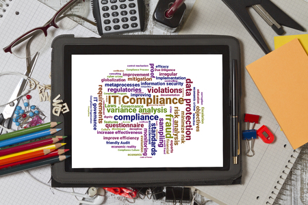 mitigation: Tablet screen with IT compliance word cloud shaped as a circle