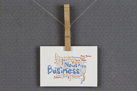 Business news word cloud on a business card pinned up on a board