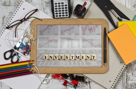 Blackboard with Investment word on business newspaper
