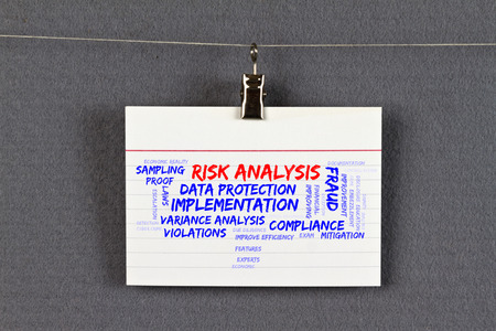 risk analysis: risk analysis word cloud on a business card pinned up on a board