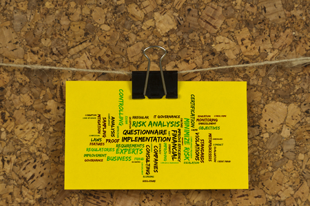 risk analysis: note pad with risk analysis word cloud on a cork pinboard