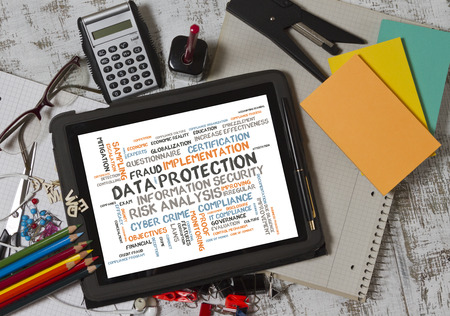 escalation: concept of data protection word cloud on tablet pc screen with note pad, pencils and calculator Stock Photo