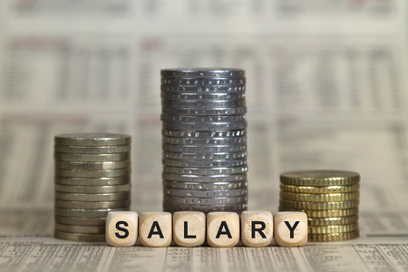 Salary winner's pedestal from coins on a business newspaper