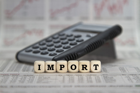 Import word built with cubes in front of a calculator on a business newspaper